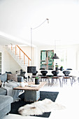 Grey sofa in front of dining table and chairs in open-plan interior