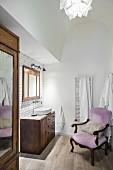 Alter Sessel mit rosafarbenem Bezug im Bad mit dunklen Holzmöbeln