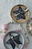 Paper star-shaped cutlery holder on plate with vintage decorations