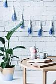 DIY Marmorierte Tassen auf Tisch, daneben Zimmerpflanze vor weisser Ziegelwand