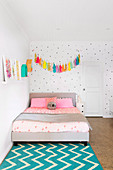 Tassel garland over the bed against a dotted wall