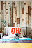 Bed with letter pillow in front of wallpaper with wooden motif