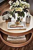 Cosmetics and small bouquet on coffee table