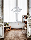 Freestanding bathtub in front of window, designer chandelier above, round table and metal chair in bathroom