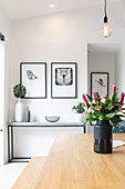 Bouquet of flowers in black vase on the wooden table in the dining room