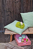 Lady's mantle and roses on cushion with green gingham cover
