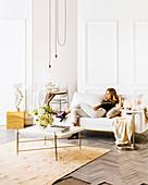 Junge Frau auf weißer Couch vor weißer Kassettenverkleidung, im Vordergrund Couchtisch mit weißer Blumenstrauß