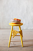 Stack of plates and paper rosettes on yellow stool