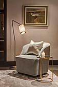 Atmospheric lighting around armchair and small gilt side table