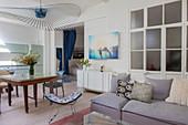 Graues Polstersofa mit Kissen vor Zwischentür mit Glaseinsatz, Klassikerstuhl, Esstisch und Küche in offenem Wohrnaum