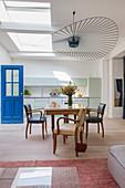 Esstisch mit Armlehnstühlen, darüber Designerleuchte, im Hintergrund mintfarbene Küchenzeile