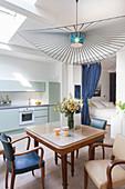 Esstisch mit Armlehnstühlen, darüber Designerleuchte, im Hintergrund mintfarbene Küchenzeile und Vorhang vor Schlafbereich