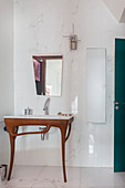 Designer washstand below mirror mounted on marble wall tiles