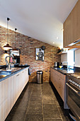 Kitchen worksurface opposite long counter in converted barn with brick wall