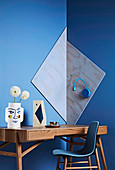 Desk and chair against blue wall with geometric decoration