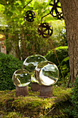 Glass spheres on rusty metal stands decorating garden