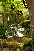 Glaskugeln auf rostigen Blechdosen als Gartendekoration