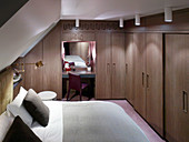 Double bed and dark fitted wardrobes in bedroom