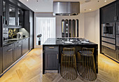 Elegant kitchen with black cabinets and island counter, Ten Trinity Square, London