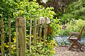 Staketenzaun aus Kastanienholz, im Hintergrund Gartenstühle auf Kiesfläche