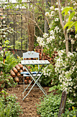 Folding table and chair in greenhouse of old nursery surrounded by white flowers