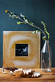 Black-and-white photo in hand-made frame and dried flowers in bottle