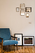 Blue armchair next to framed photos and collection of mirrors mounted on wall