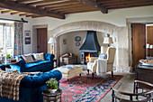 Kamin in Nische, heller Sessel und blaue Sofagarnitur in historischem Wohnzimmer