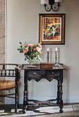 Rosenstrauß, Holzkästchen und Kerzen auf antikem Wandtisch mit Holzschnitzerei
