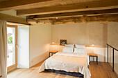 Rustic wood-beamed ceiling in simple bedroom