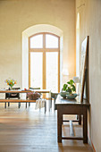 Light flooding into dining room through tall arched window