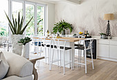 Delicate barstools at kitchen counter in open-plan interior with palm-tree-patterned wallpaper