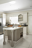 L-shaped counter in renovated country-house-style kitchen in shades of white and taupe