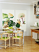 Wooden chairs with turned legs and green seat cushions around dining table in front of large botanical artworks