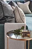 Glass side table next to sofa with scatter cushions