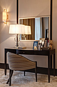Upholstered chair at dressing table with lamp and photos in bedroom