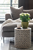 Potted chrysanthemum on cylindrical side table in front of grey sofa