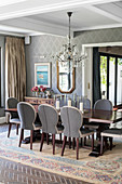 Table, elegant chairs, chandelier and patterned wallpaper in dining room