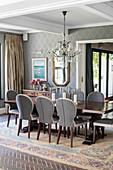 Esszimmer mit Tisch, eleganten Stühlen, Kronleuchter und tapezierter Wand
