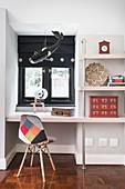 Wandregal mit eingebautem Schreibtisch und Stuhl mit buntem Bezug vor Fenster