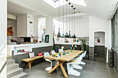 Wooden table and designer chairs in open-plan dining area with grey floor tiles