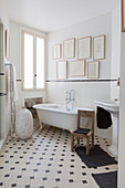 Vintage-style bathroom with gallery of pictures on wall and black-and-white patterned floor