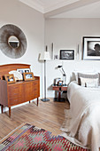 Old chest of drawers below sunburst mirror in bedroom