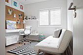 White sofa bed and black and white striped rug in study