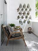 Holz-Armlehnstühle mit Auflagen auf Balkon mit schwarz-weissen Fliesen, Grünpflanzen an der Wand