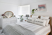Double bed and chest of drawers in simple white bedroom