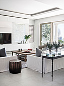 White sofas, console table at back of sofa and terrace doors in bright living room