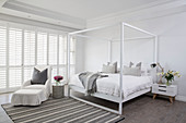 Simple four-poster bed and armchair with footstool in white bedroom