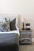 Scatter cushions on double bed with houndstooth headboard and bedside table in simple guest room
