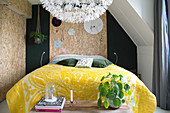 Yellow felt blanket on bed in bedroom with chipboard panels on walls